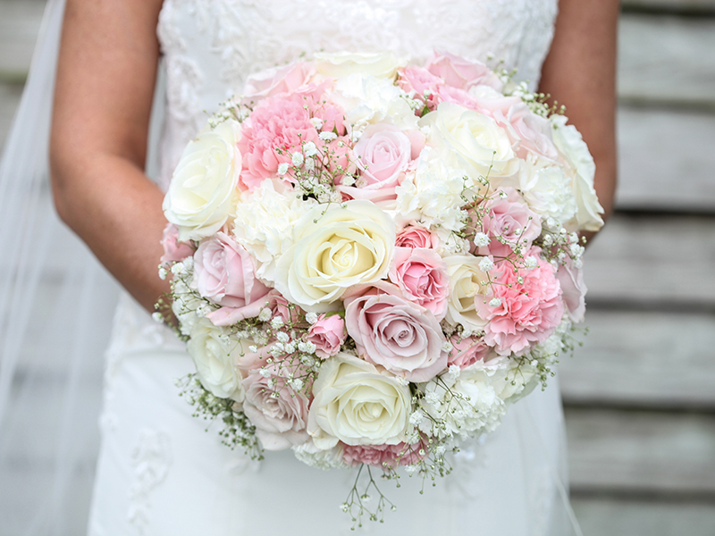 A round wedding bouquet with pink, lavender and white roses