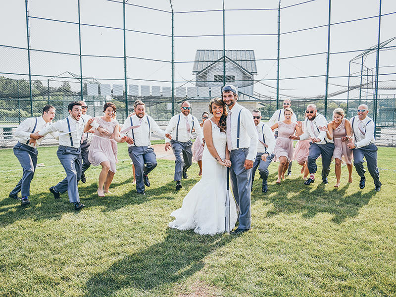 A photo of a bridal party at a ballfield. The bridal party is running to the bride and groom.