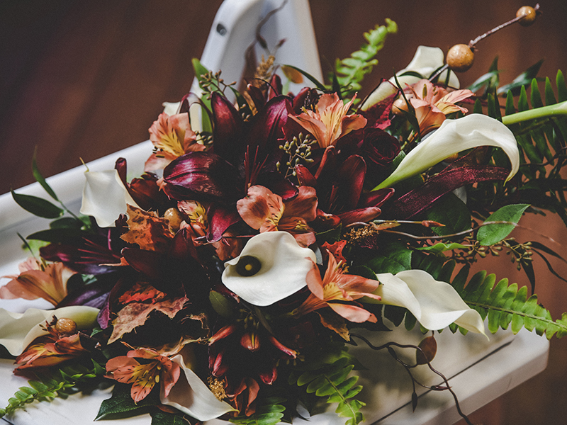 A photo of a fall inspired wedding bouquet with calla and tiger lilies and ferns