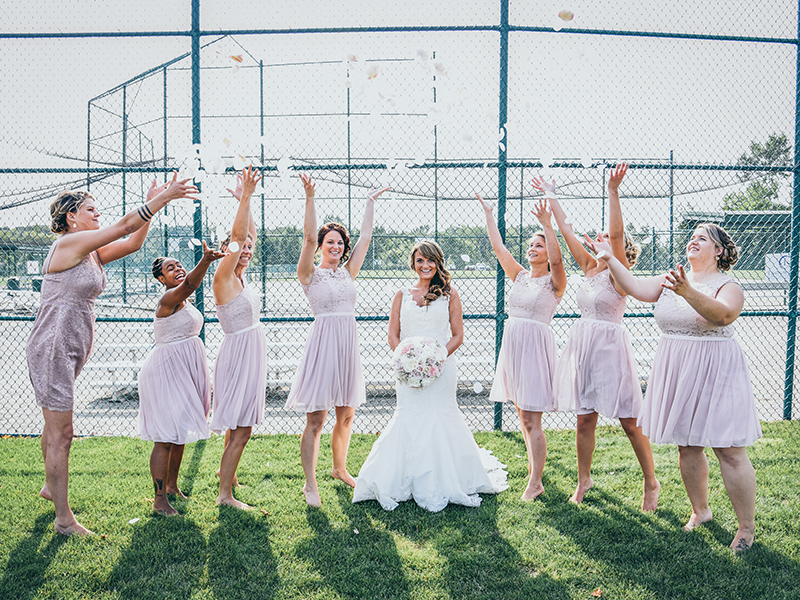 A photo of bridesmaids throwing rose petals into the air around the bride.