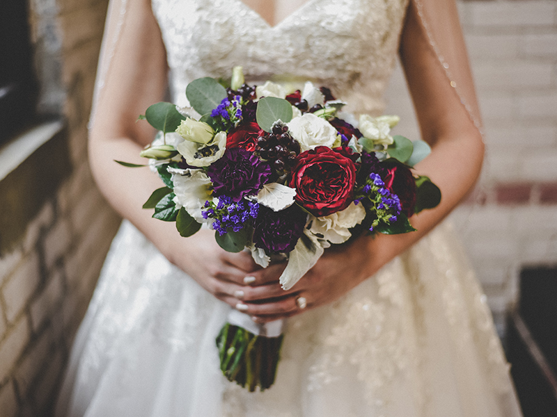 A photo of a bride with a jewel toned wedding bouquet.