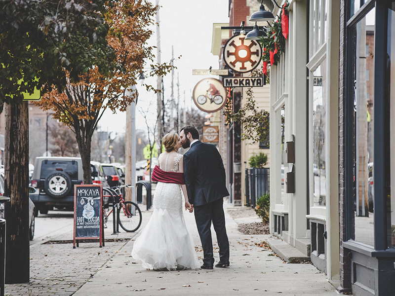 A photo of a couple kissing on a sidewalk in the city