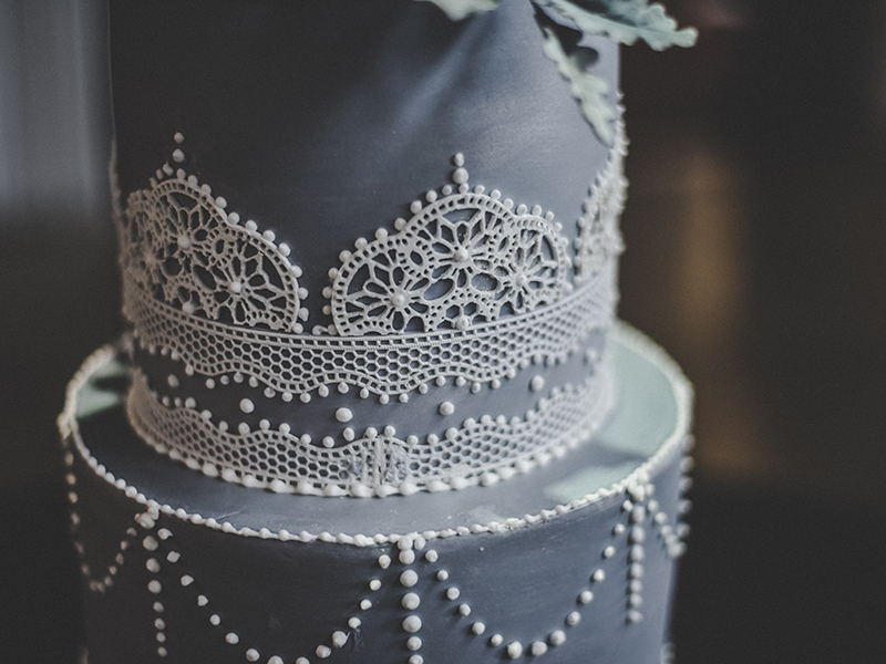 A photo of a beautiful wedding cake with lace details