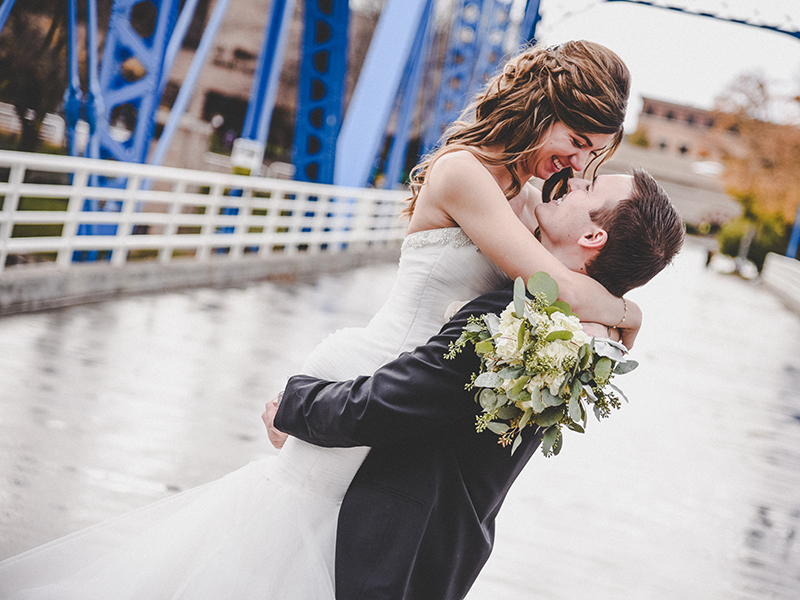 A groom spinning his bride in his arms on a winter bridge