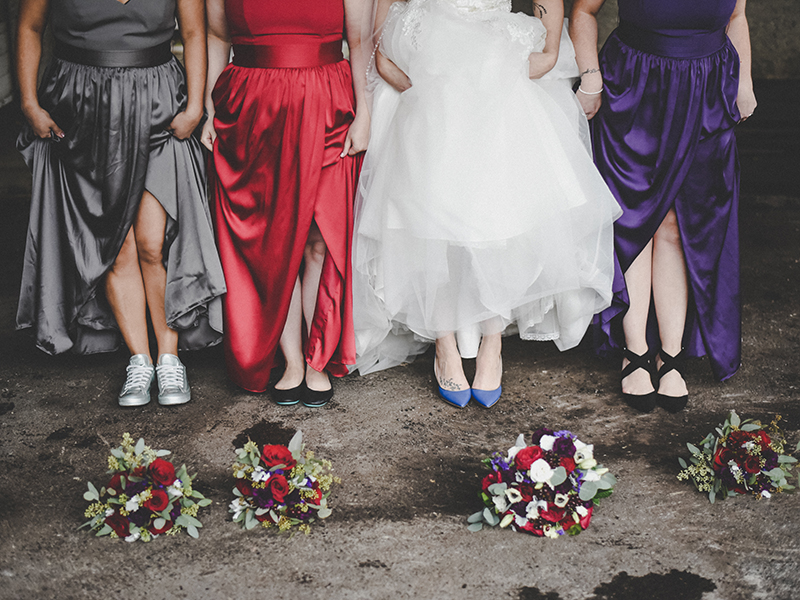 A photo of a bride and her bridesmaids showing their legs and shoes. One has tennis shoes.