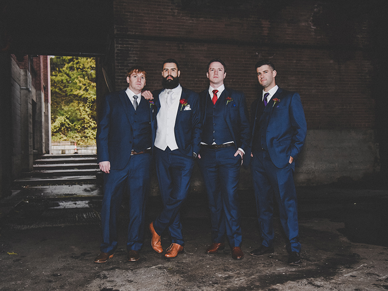 A photo of a groom and three groomsmen in a dark alley