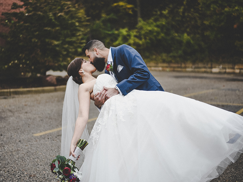 A photo of a groom dipping his bride to kiss her.