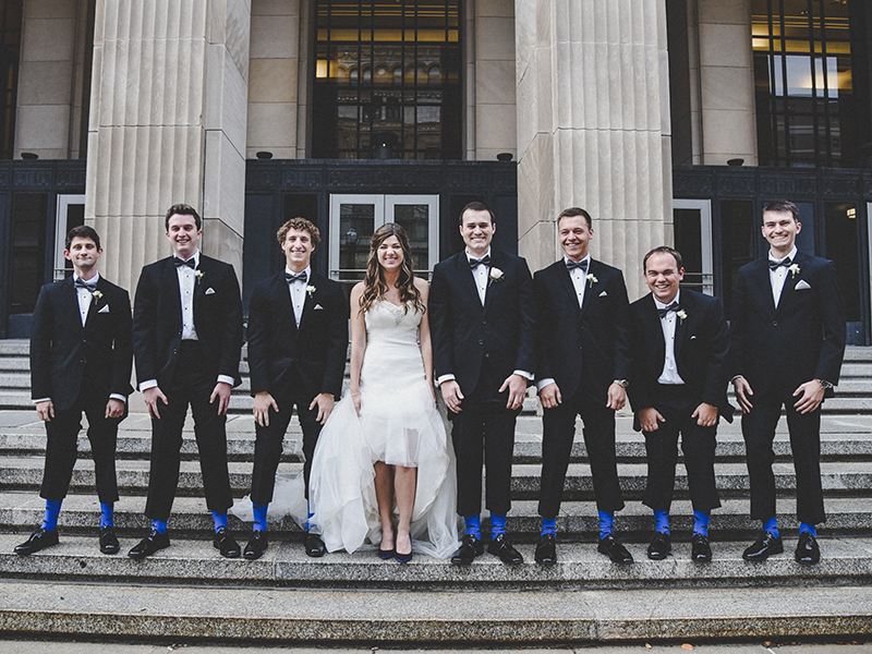 A bride and the groomsmen on the steps of the Civic Theater in Grand Rapids