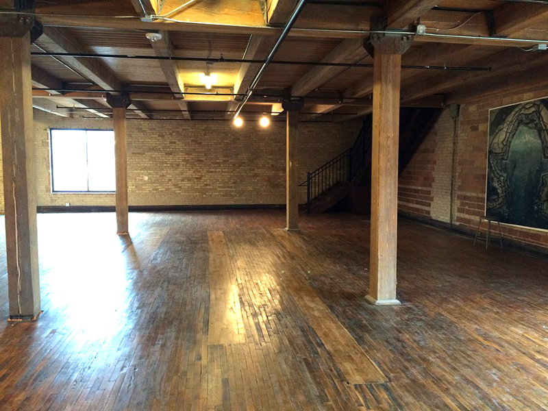 A photo of an empty ballroom in an old brick building with big wooden beams