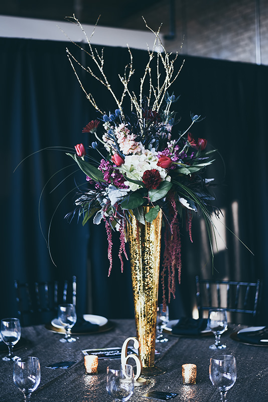 wedding reception table centerpiece. Gold vase with bold jewel toned flowers