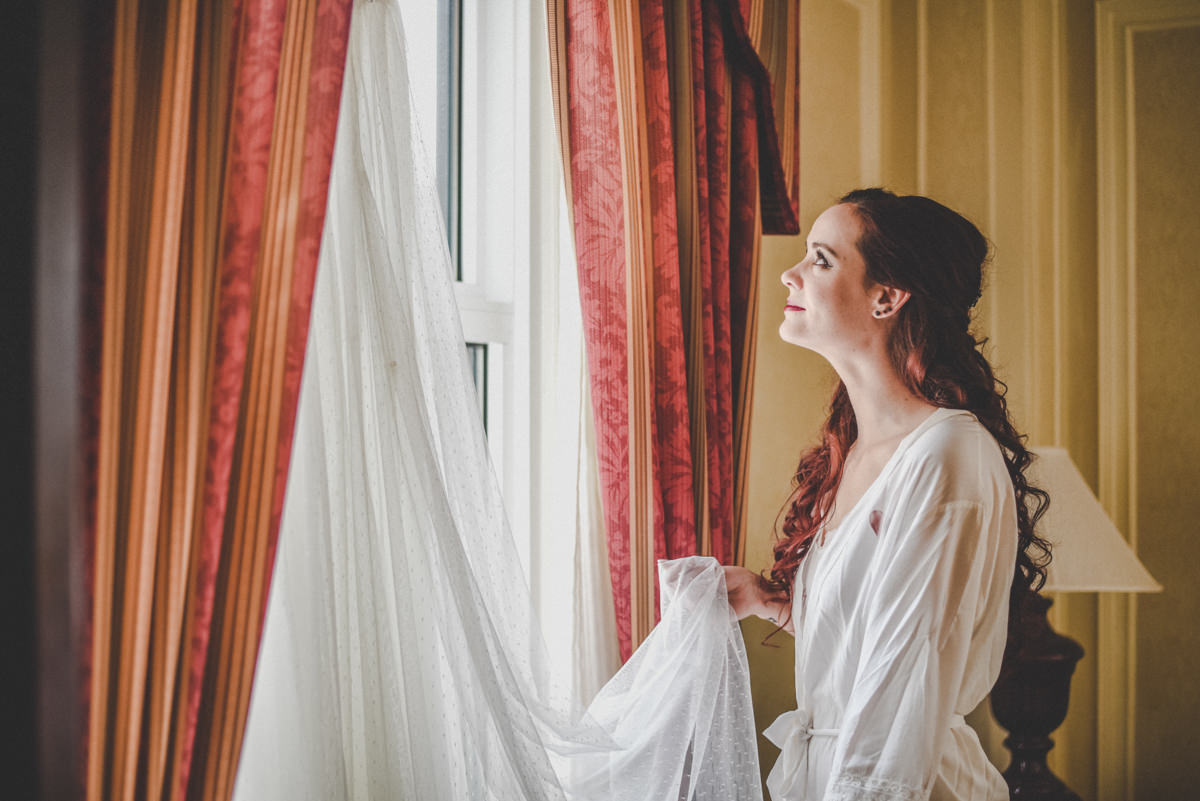 Beautiful bride looking out filmy white curtains as she gets ready for her wedding day.