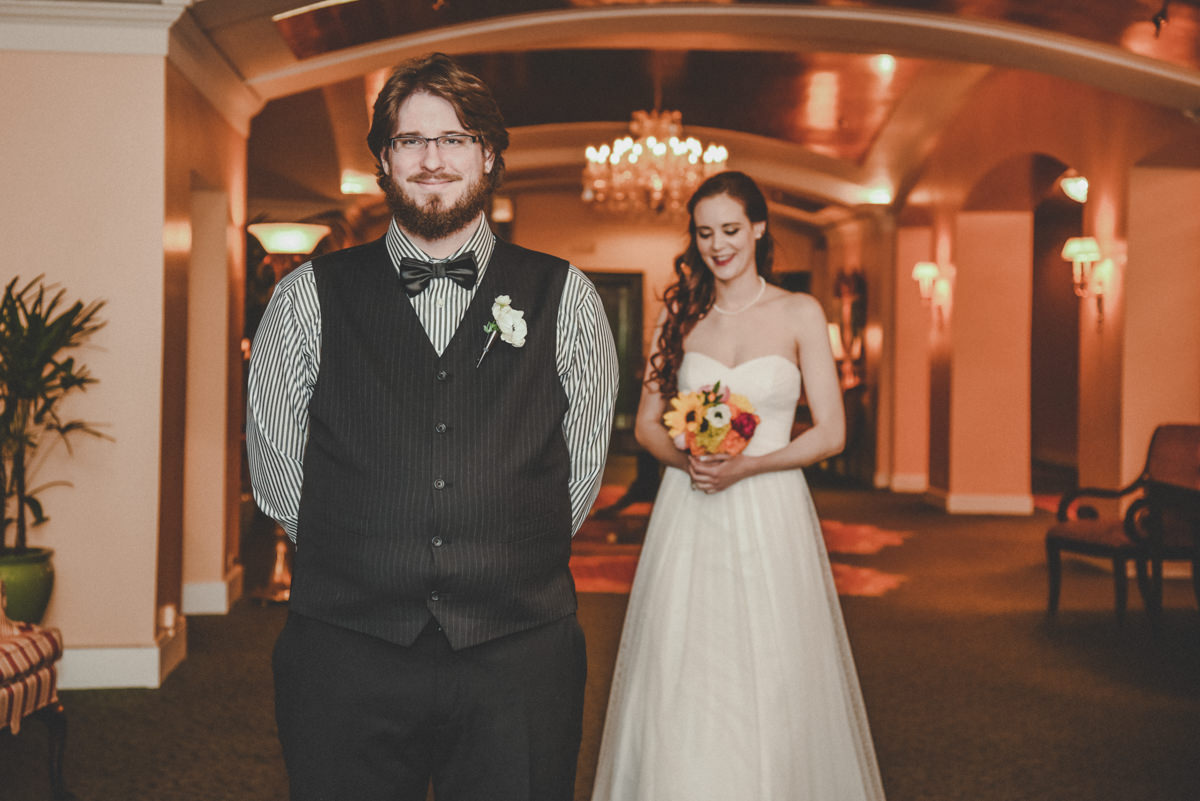 Bride walking up to groom in a beautiful hotel to reveal herself during first look on wedding day