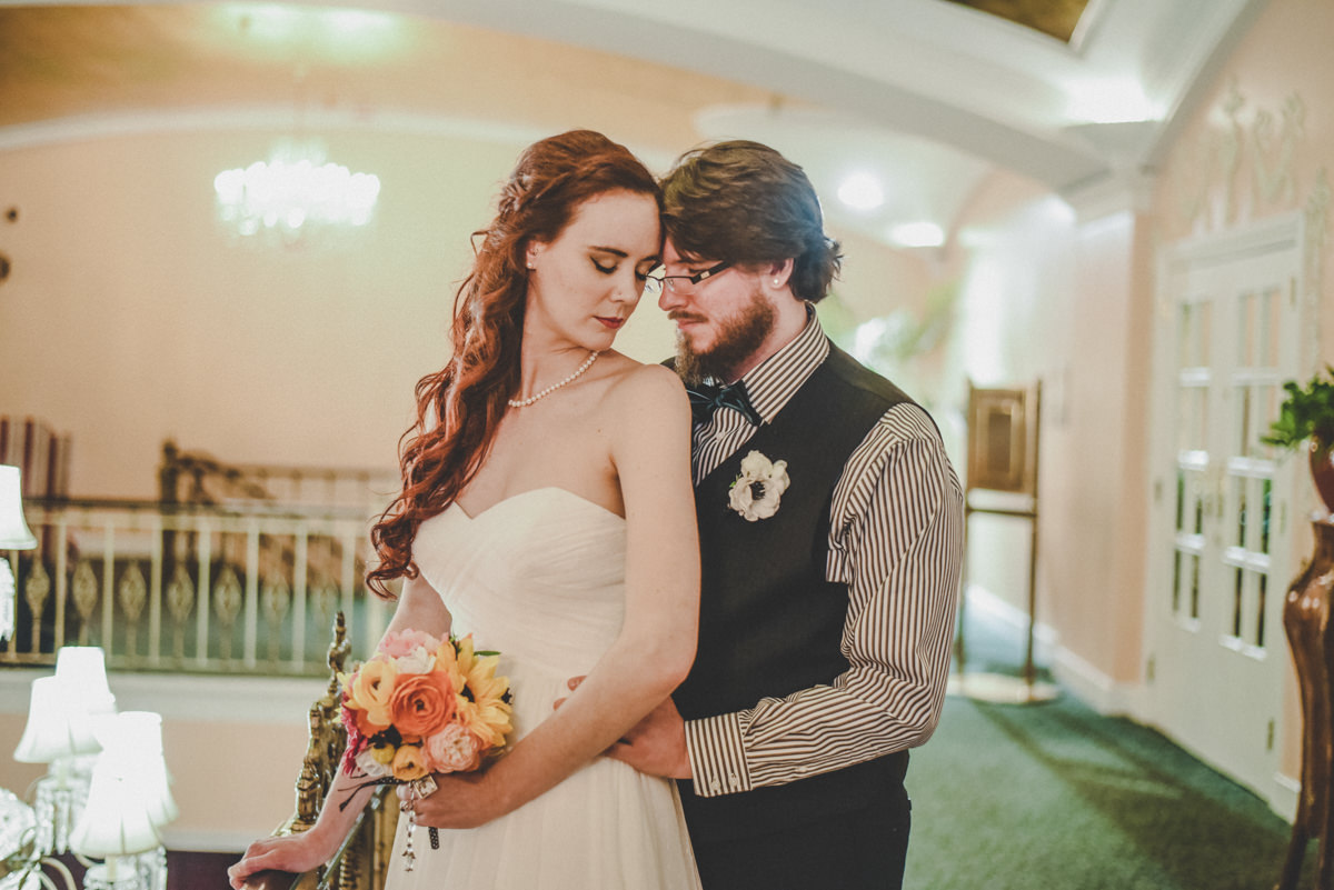 Groom holding bride at the waist as their foreheads touch