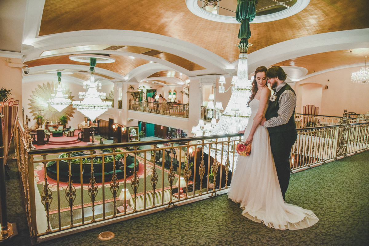 Groom holding bride while she looks down from the balcony in luxurious and historic Amway Grand Hotel