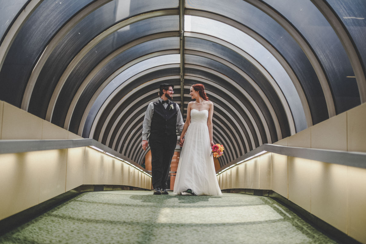 bride and groom walking across an enclosed skywalk, while looking at each other