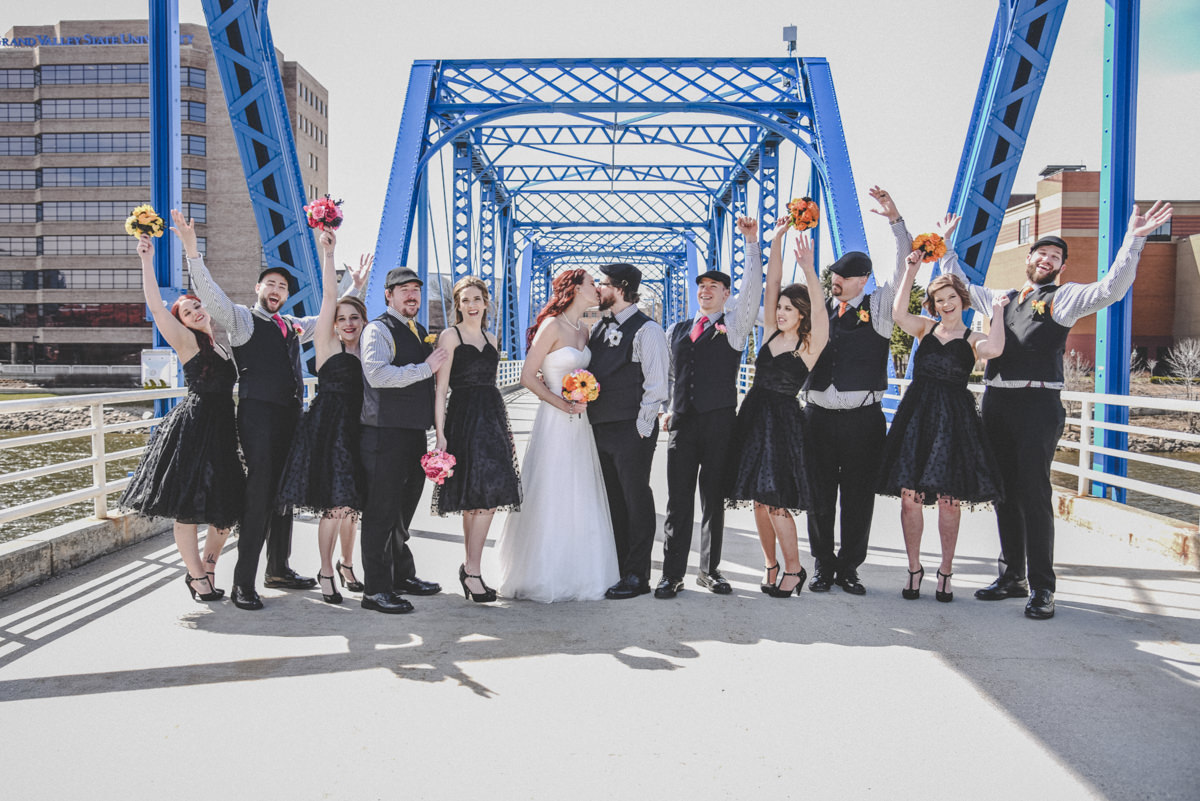 bridal party celebrating with bride and groom on a big blue bridge