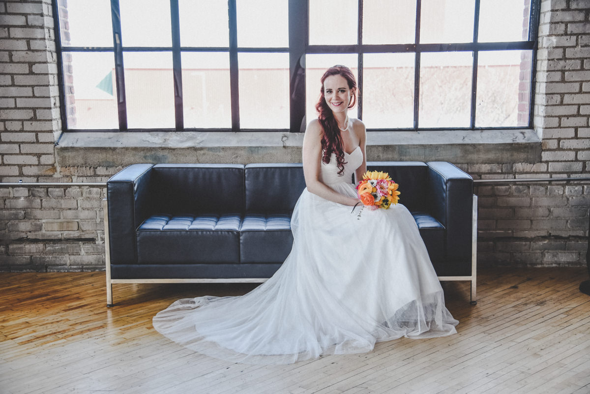 Bride sitting on a couch with her bouquet