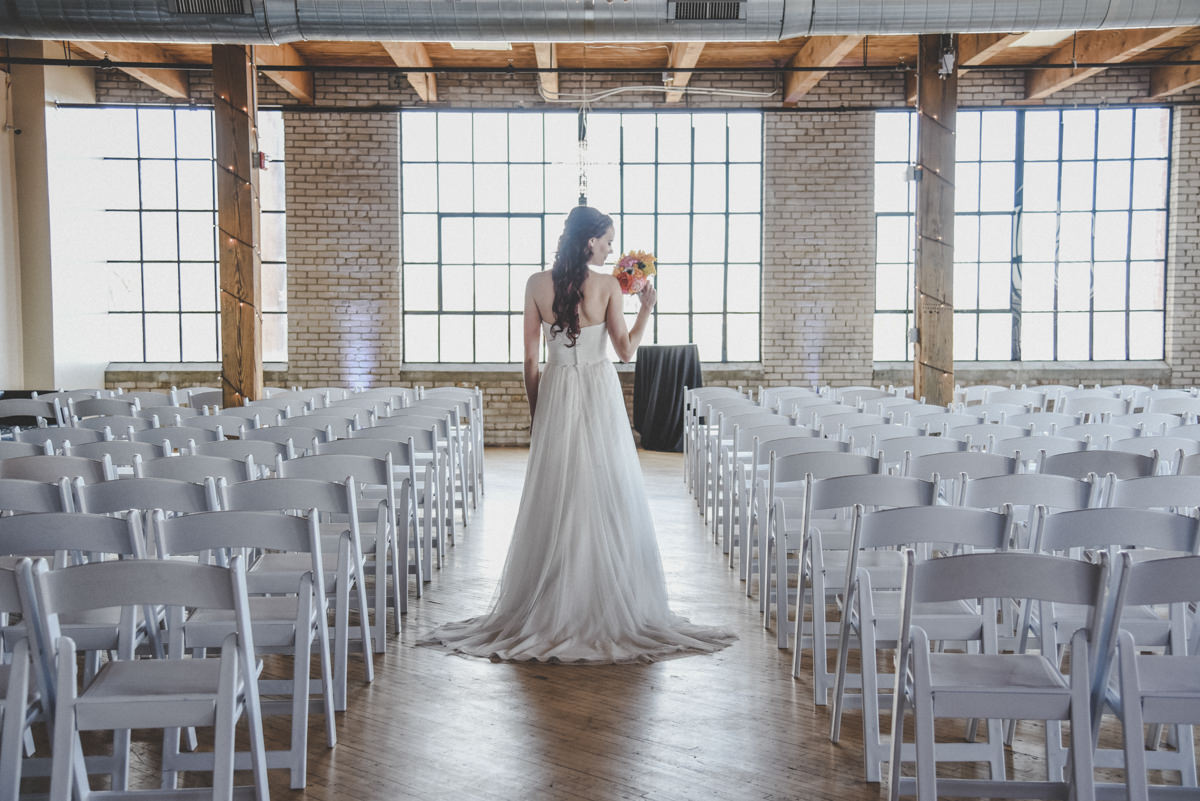Bride standing in the aisle looking at her bouquet