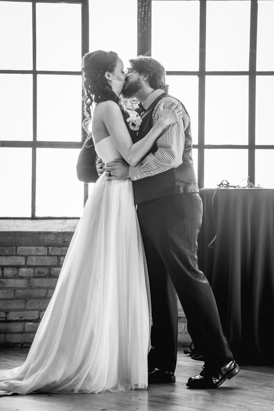 Bride and groom first kiss in an industrial loft city view ceremony