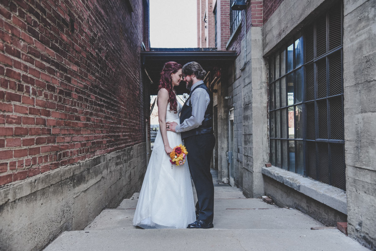 Bride and groom facing each other in a brick alley, touching foreheads and holding hands