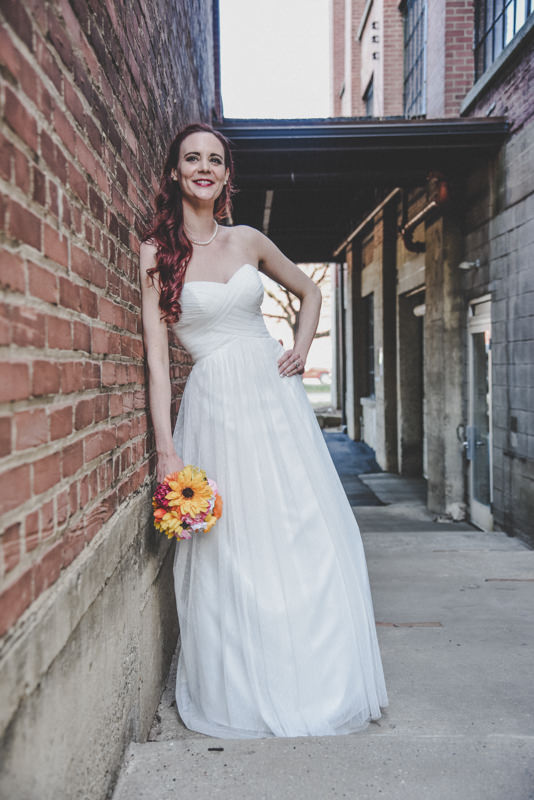 Full length image of a bride leaning against a brick wall in an alley