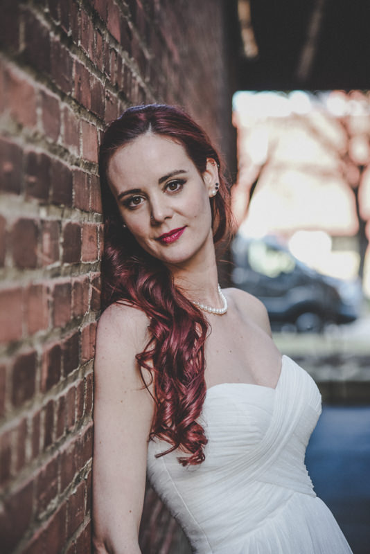 bride leaning against a brick wall in an alley