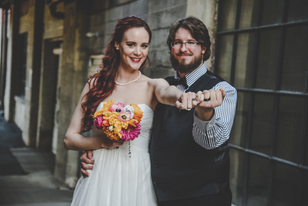 Bride and Groom close together, holding out entwined hands to show off wedding rings