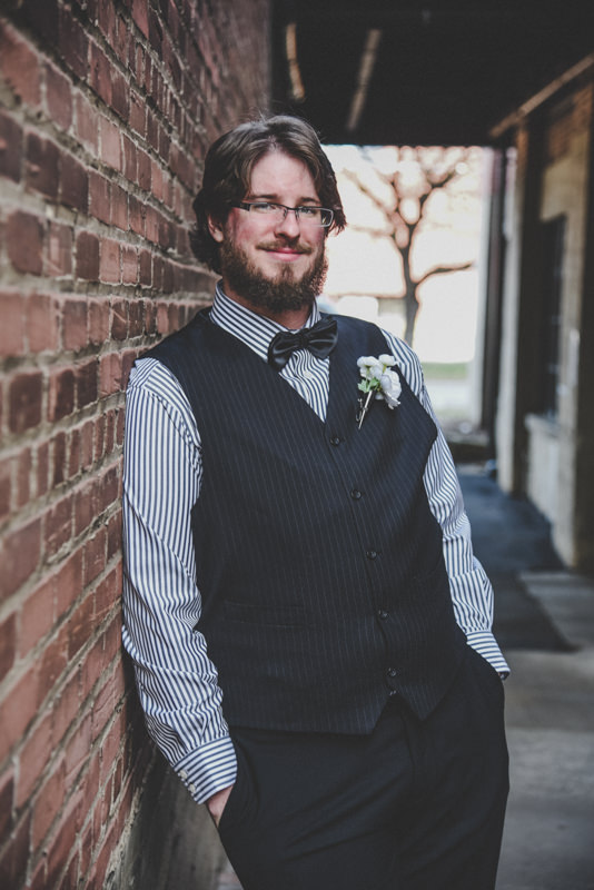 Groom leaning against a brick wall in an alley