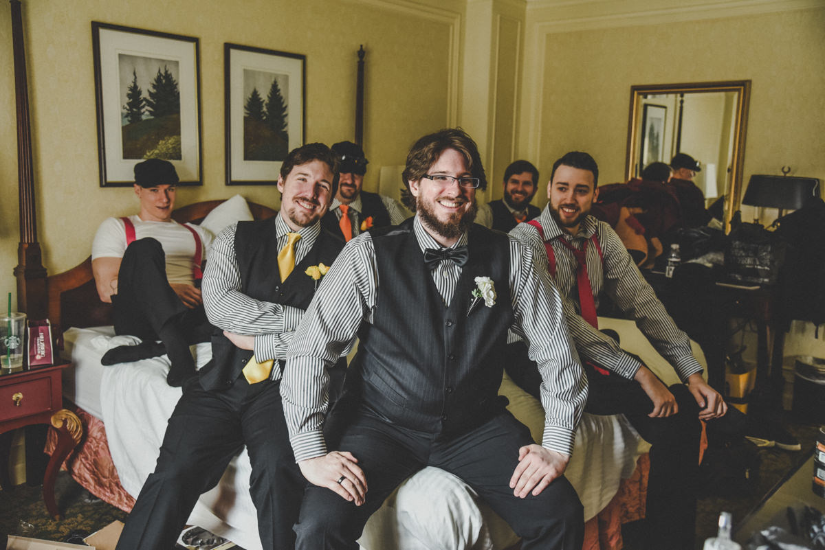 Groomsmen hanging out on bed in hotel room as they get ready for wedding day