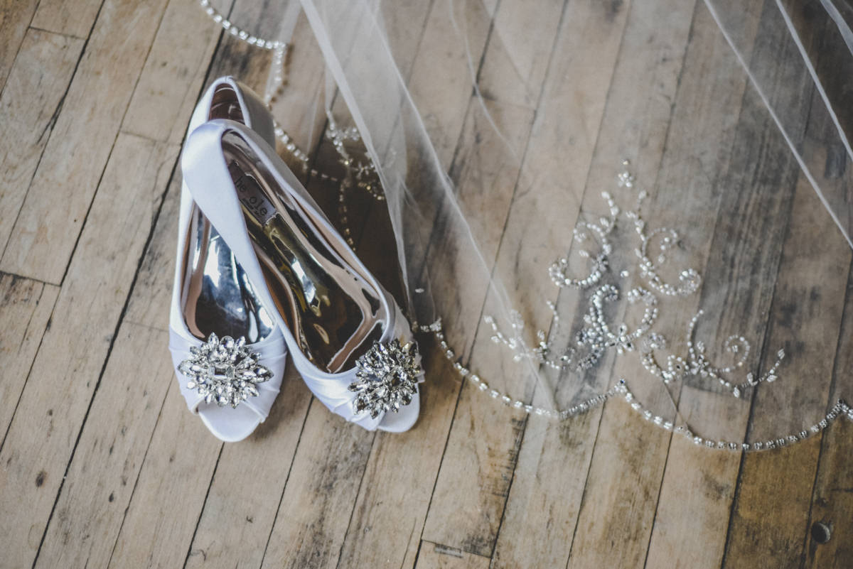 A brides silver shoes with her crystal lined veil on an old wooden floor