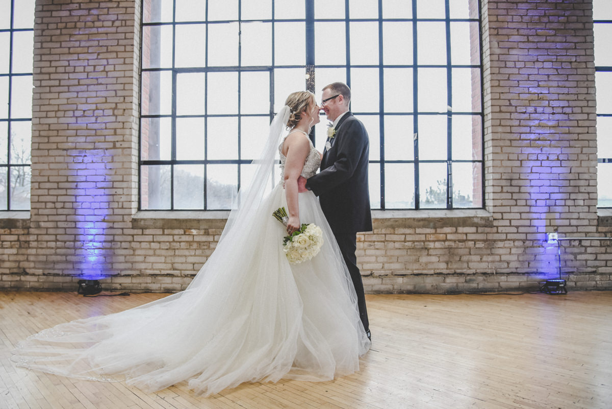 a bride and groom looking into each others eyes in front of a large window in a brick building