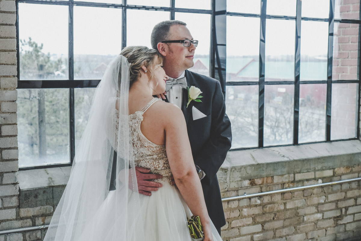 a groom holding his bride in front of a large window in a brick building