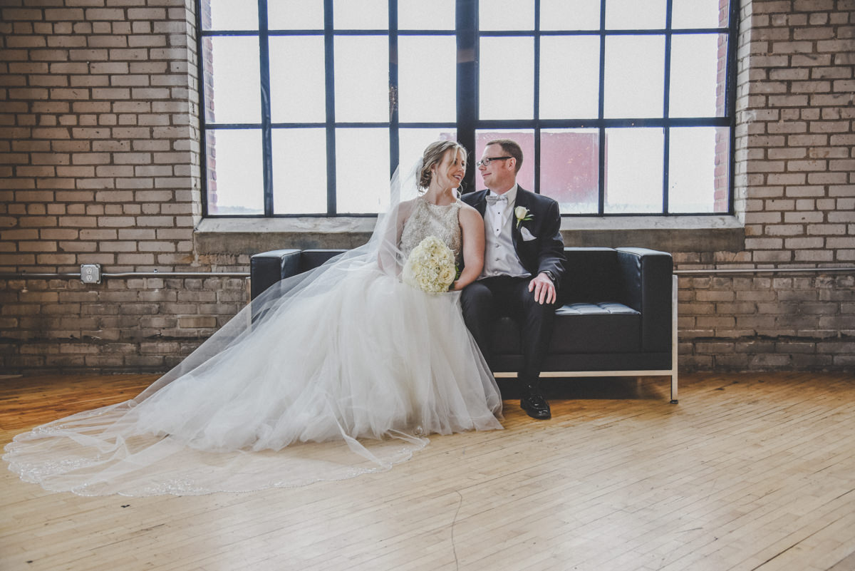 a bride with a long veil sitting next to her groom on a black couch in a brick building in front of a large window