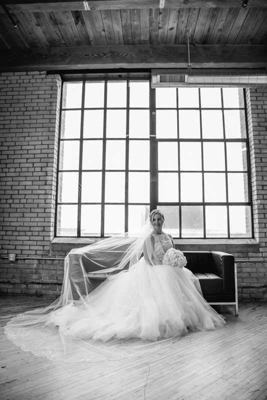 a black and white photo of a bride in a long veil sitting on a black couch in front of a large window in a brick building