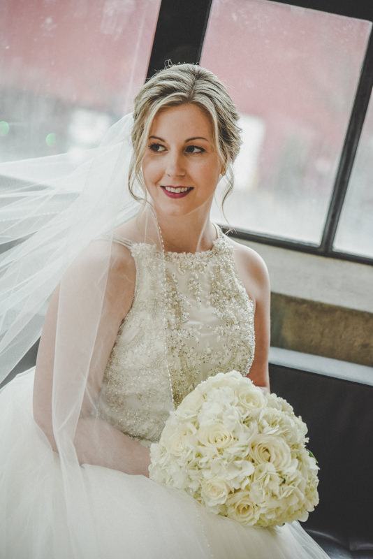 a close up photo of a bride in front of a large window
