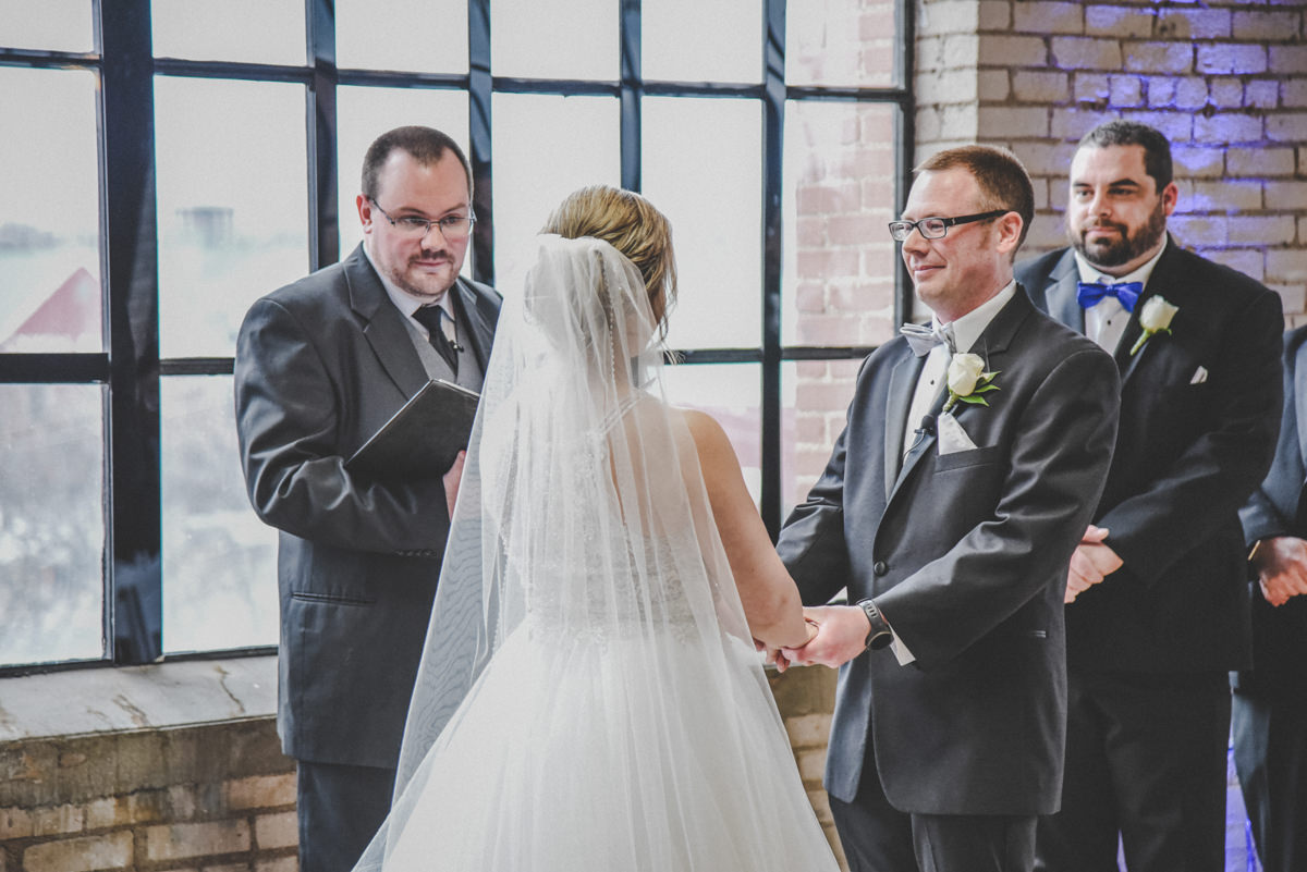 a bride and groom holding hands at the altar during their wedding ceremony