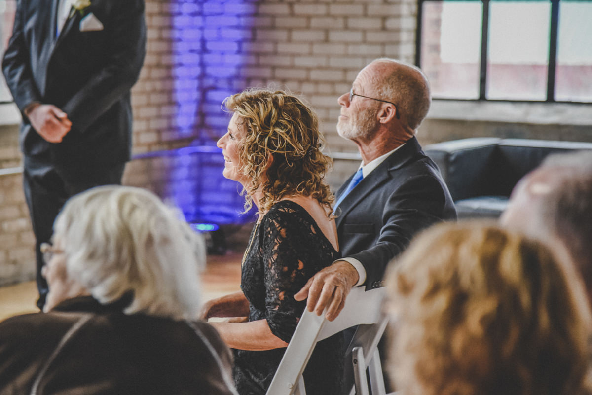 parents watching the bride and groom while seated during a wedding ceremony