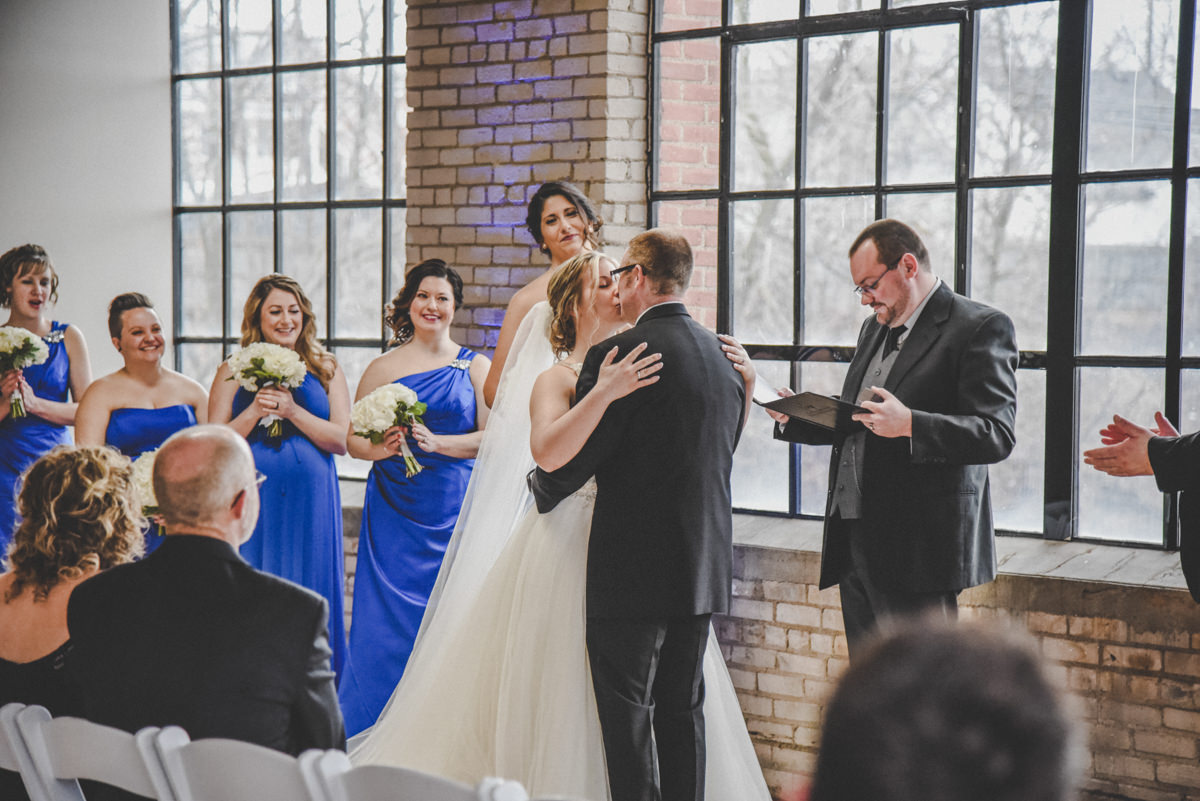 a bride and grooms first kiss in an old brick building