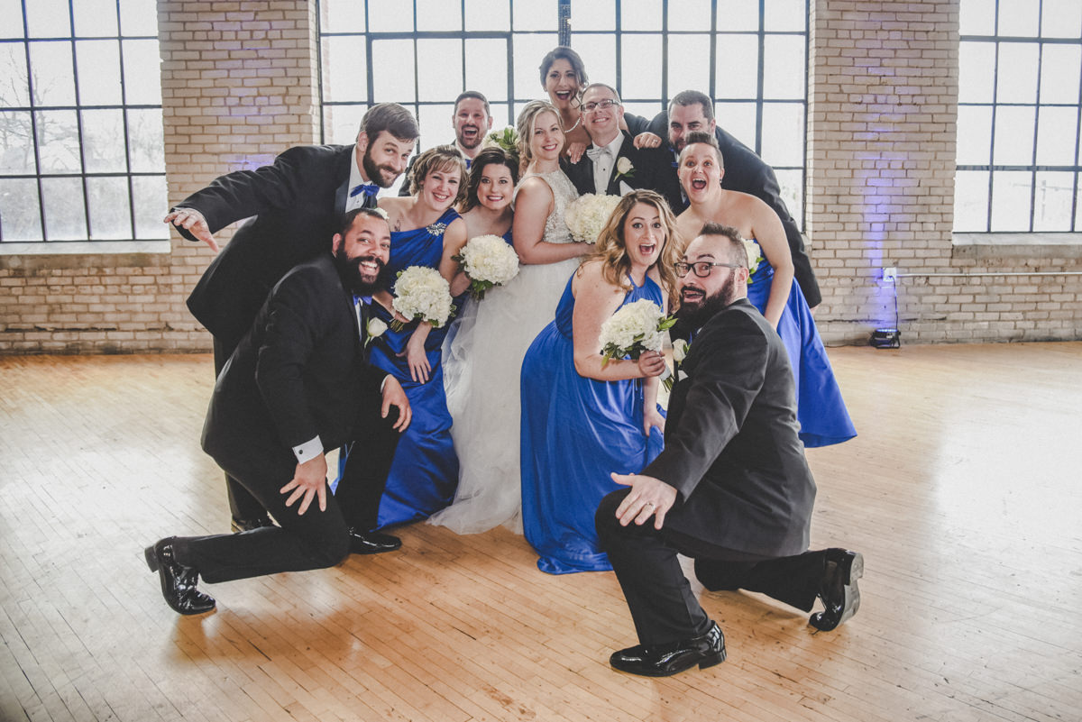bridal party laughing and running around the bride and groom