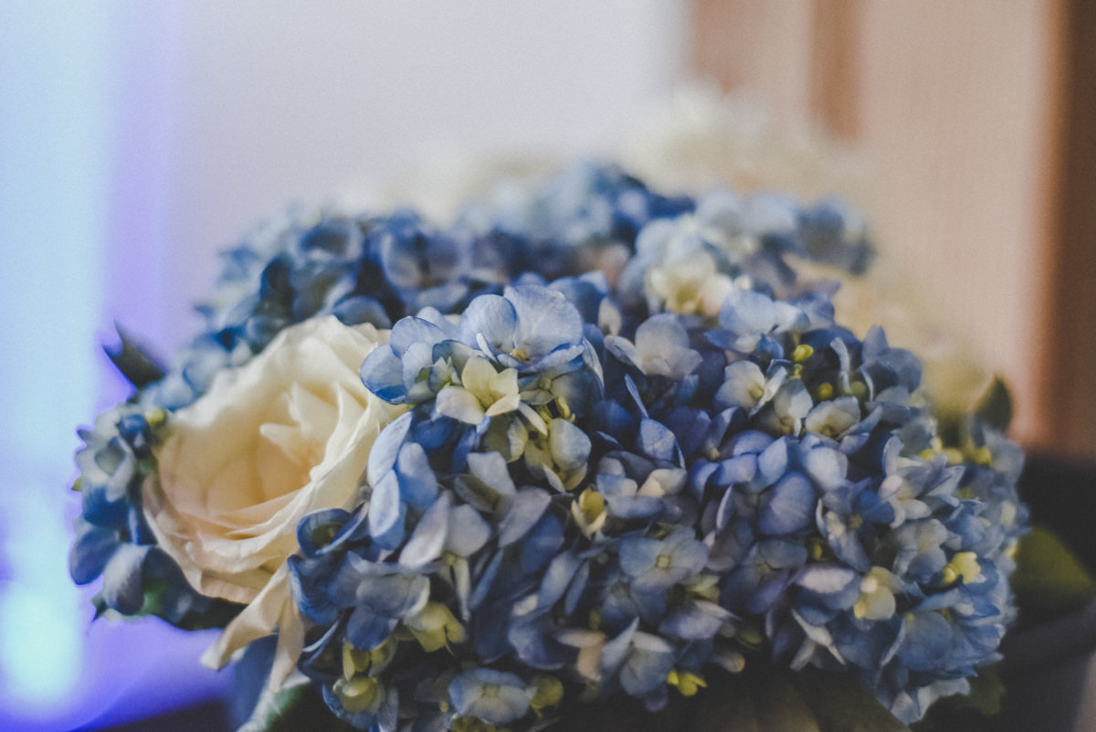 a bridesmaids bouquet of blue hydrangeas and one white rose