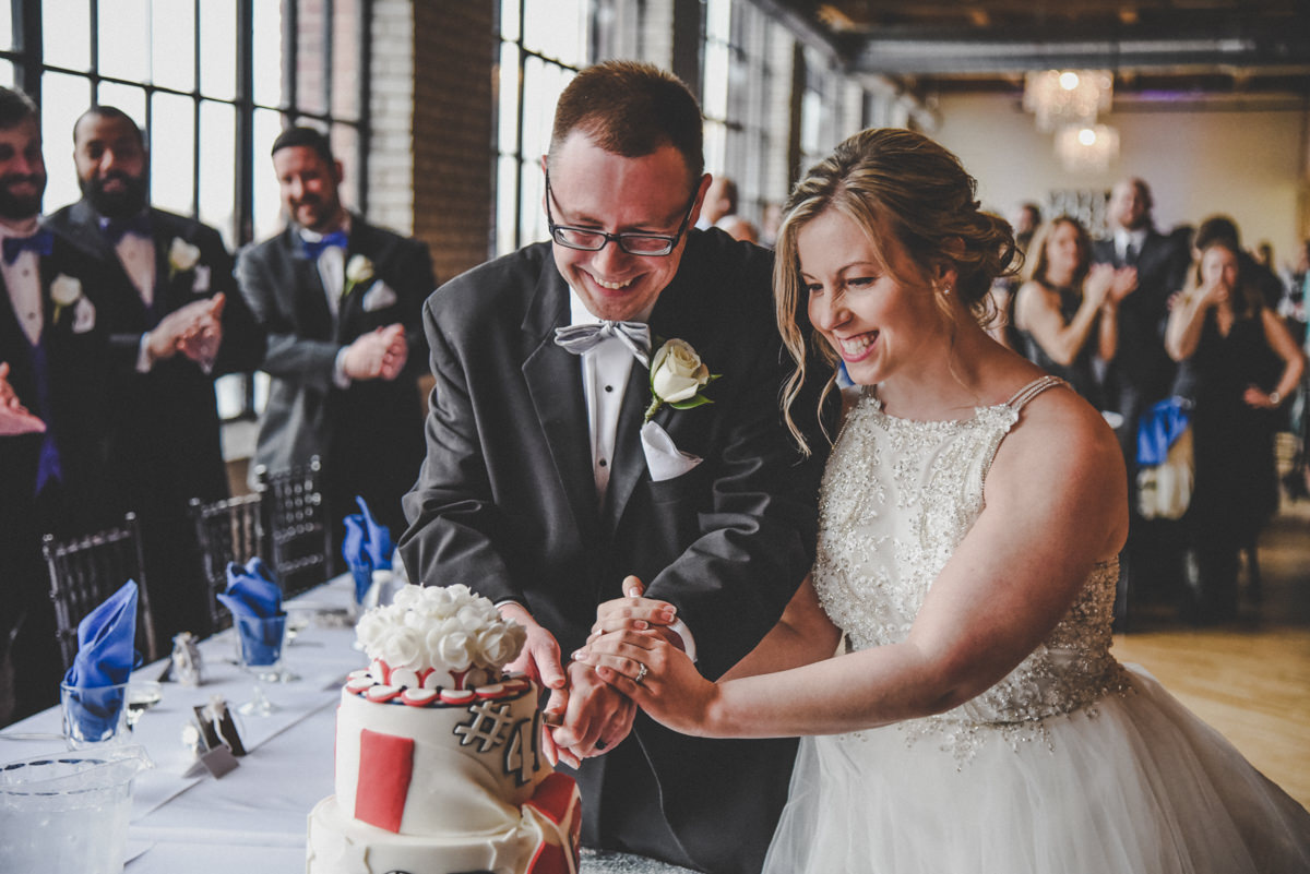 bride and groom cutting a cake in an industrial city view venue with guests