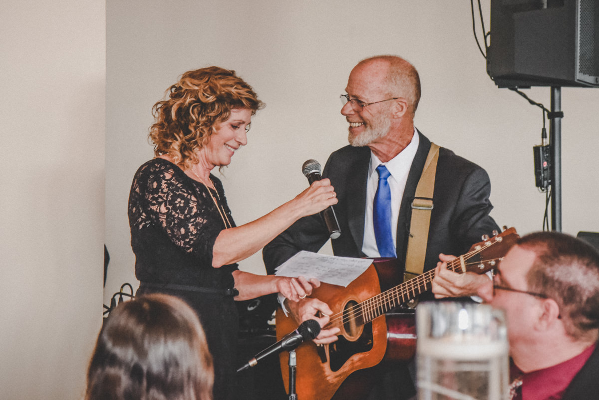parents singing while playing guitar at a wedding reception