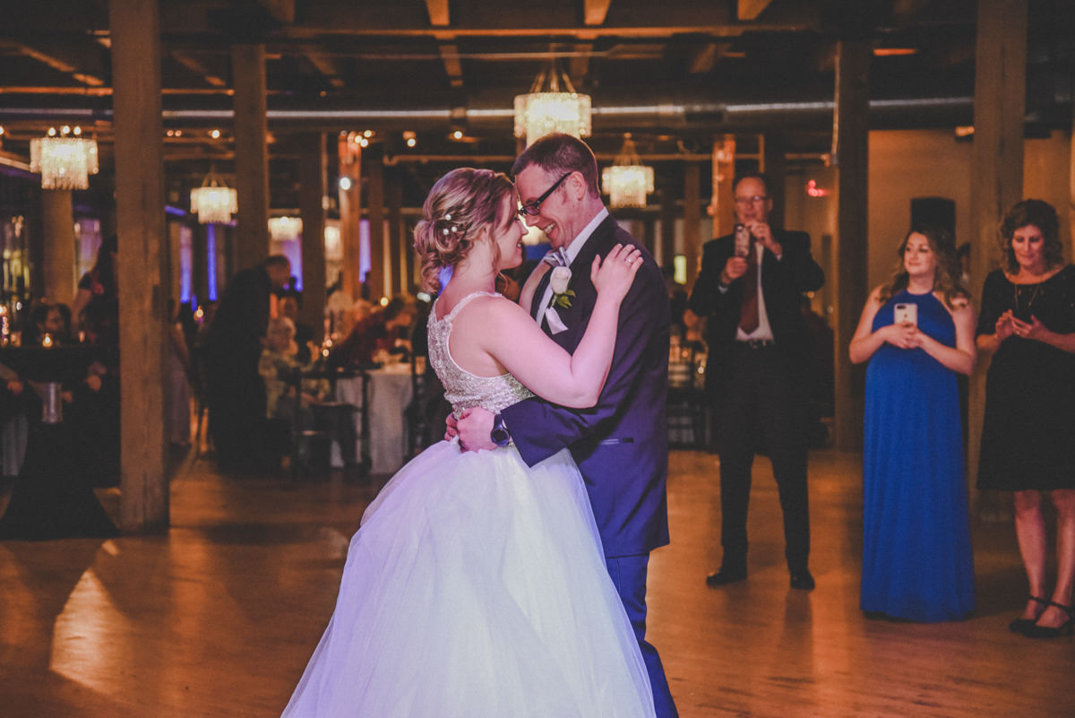 bride and groom dancing while surrounded by guests