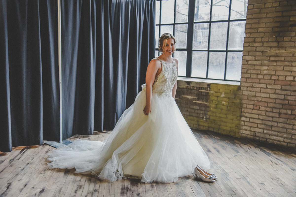 A bride getting into her wedding dress and shoes in an old industrial brick building