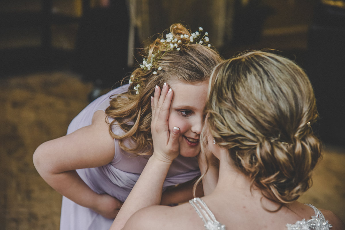 a bride holding her flower girl in a purple dress