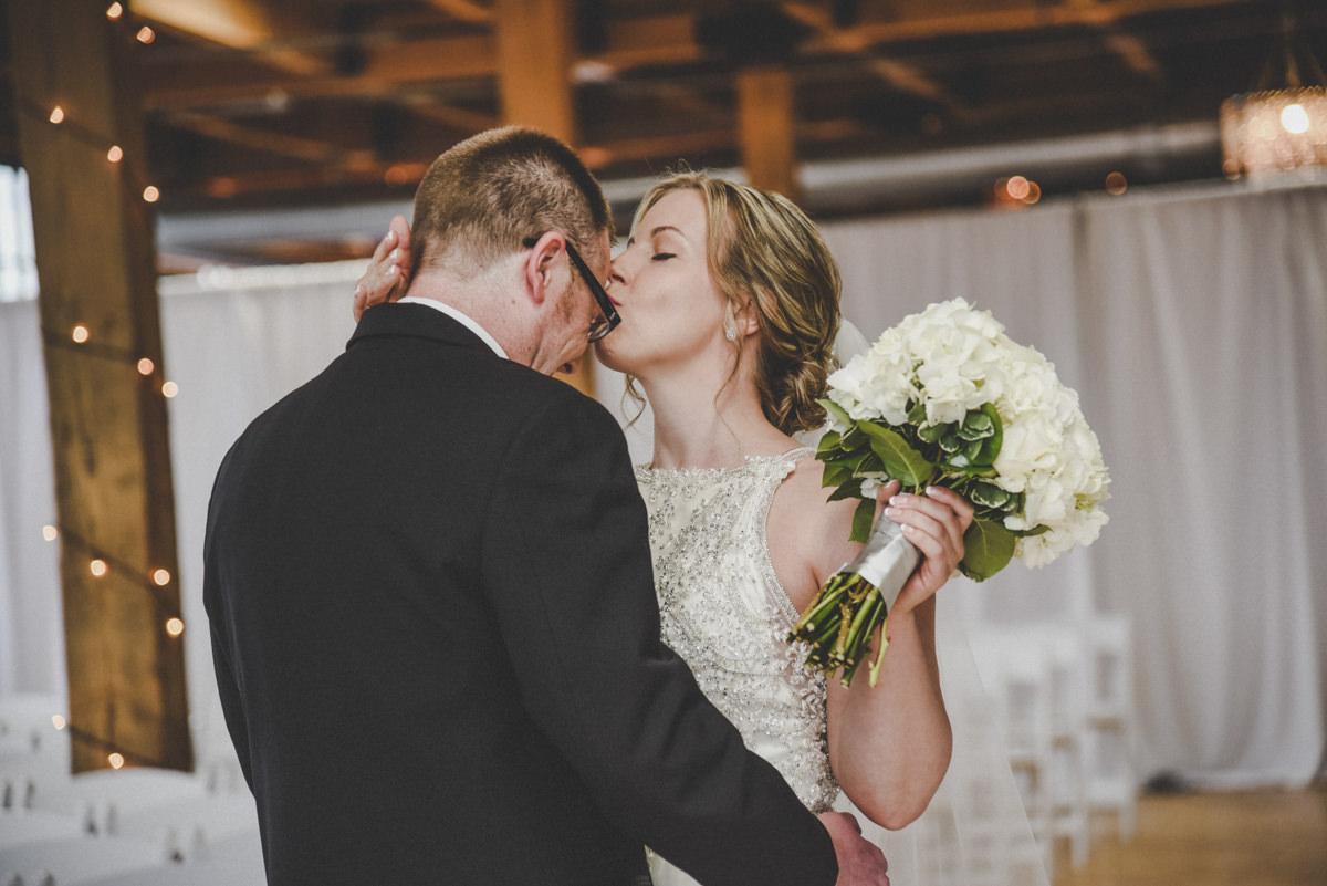 a bride kissing her groom during the first look
