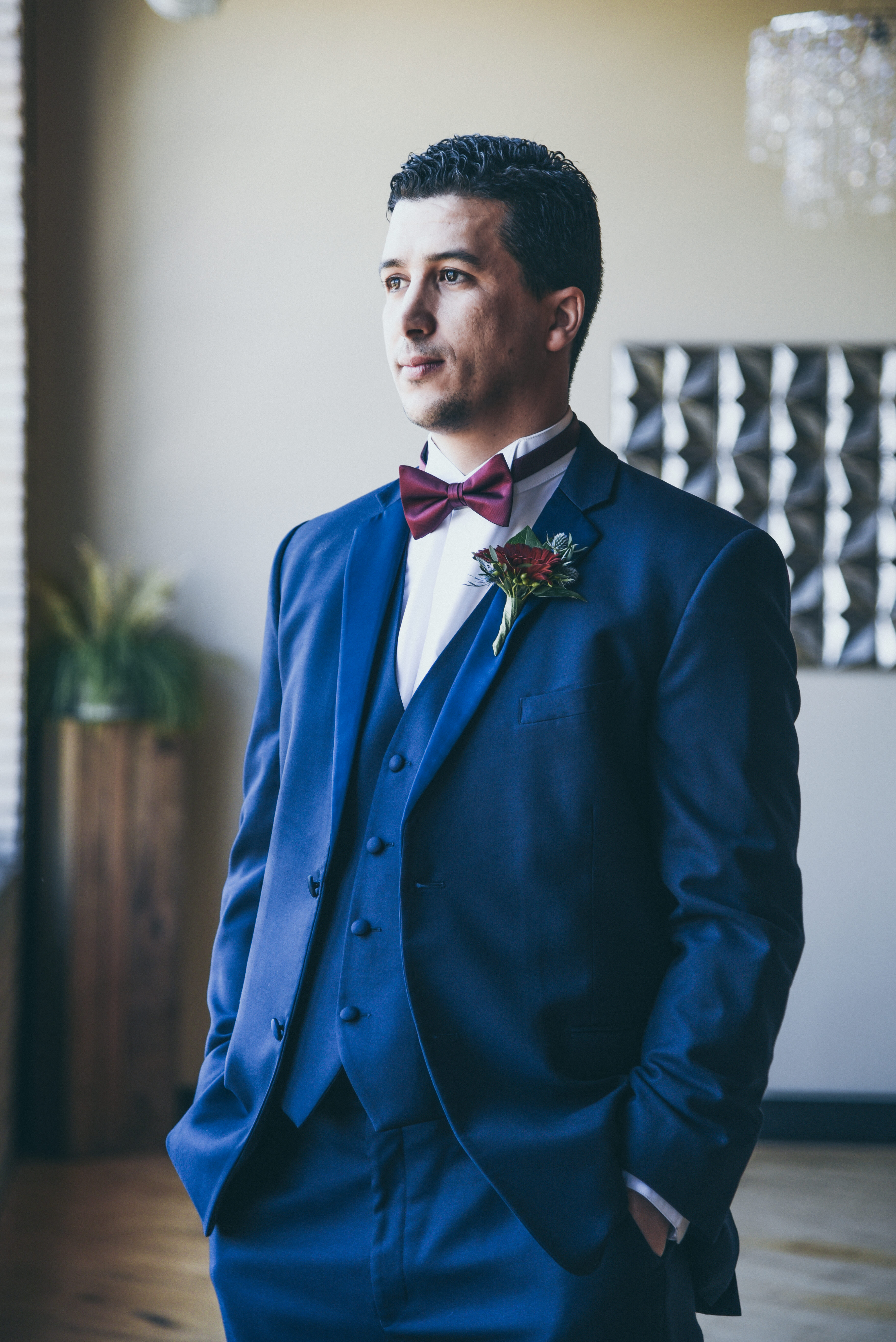 groom in navy tux with burgundy bow tie waiting for his bride