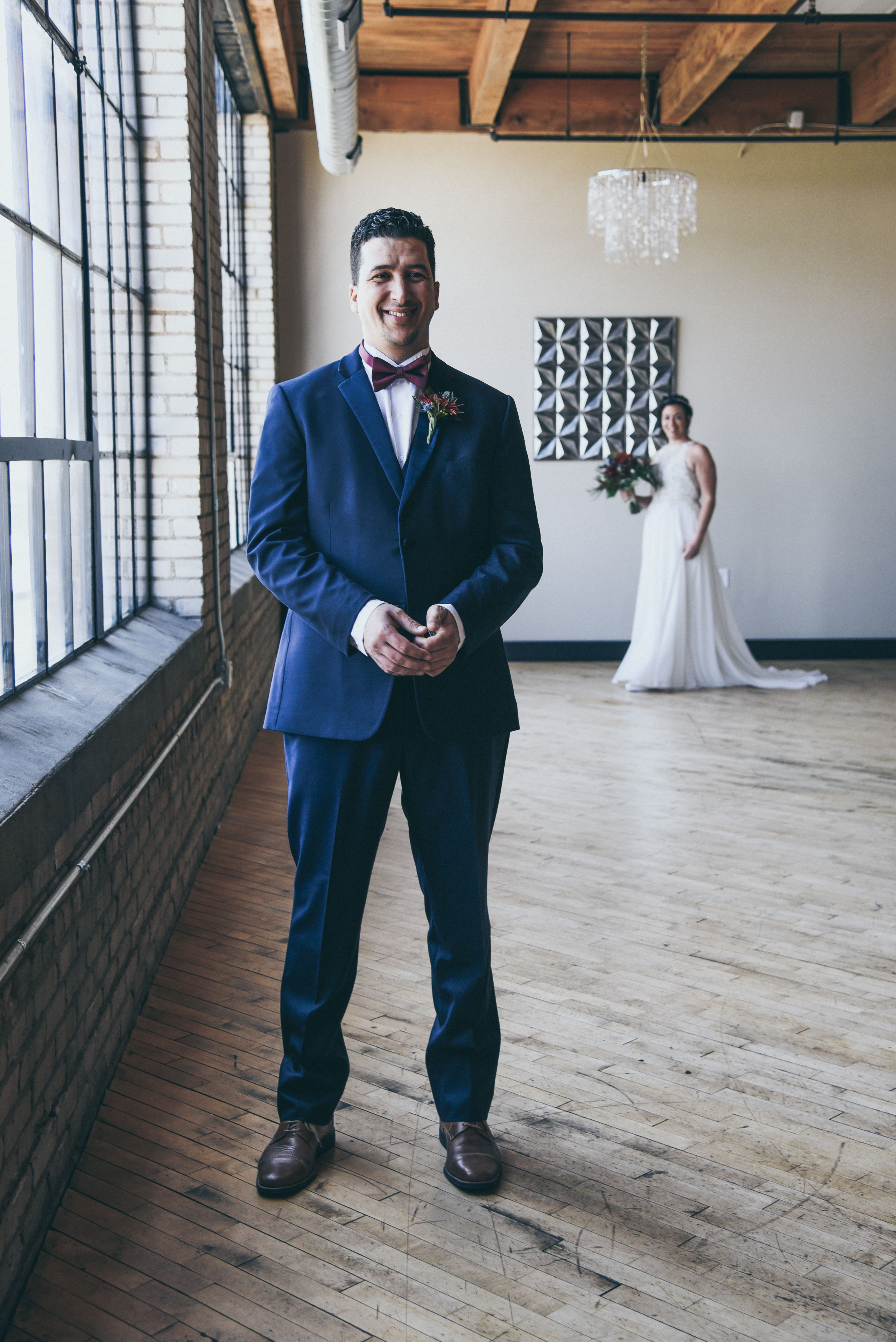 bride walking up behind groom during first look at their wedding