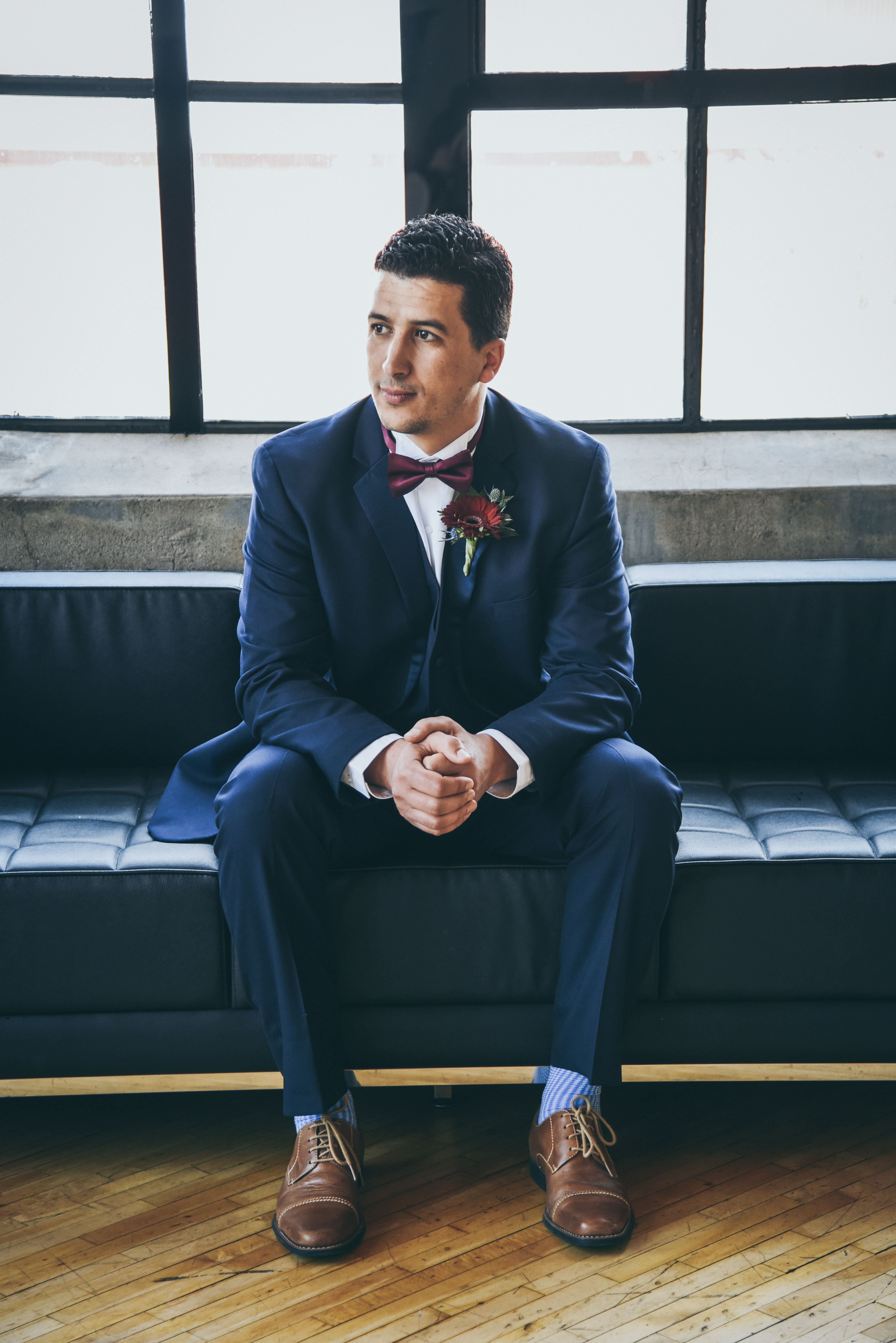 Groom in navy tux sitting on a black couch in front of a large window