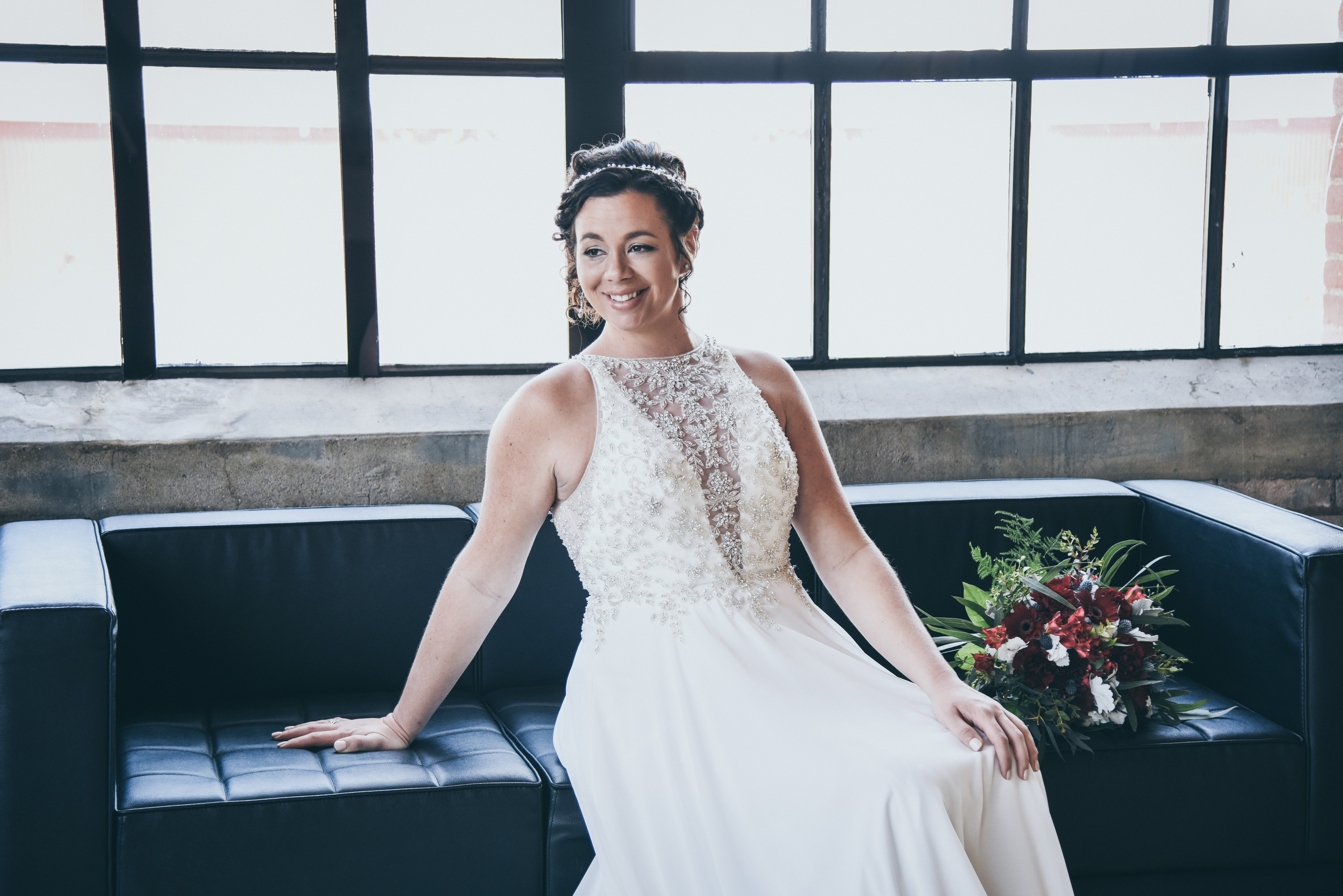 Bride sitting on a black couch in front of a large window